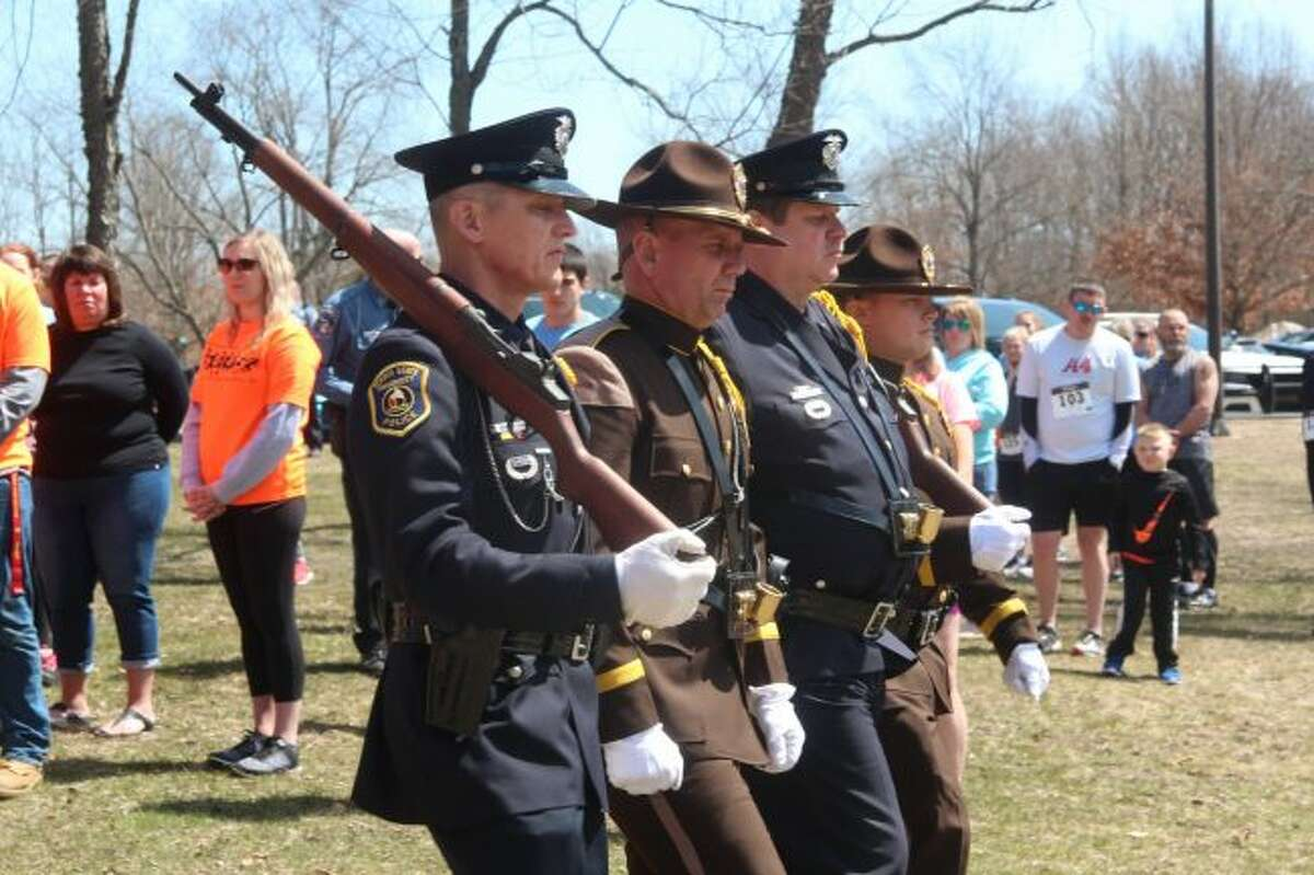 An honor guard is dismissed following the Pledge of Allegiance during Sunday's memorial service at the Fallen Officer's 5K Run/Walk Sunday afternoon at Northend Riverside Park in Big Rapids. (Pioneer photo/Brandon Fountain)