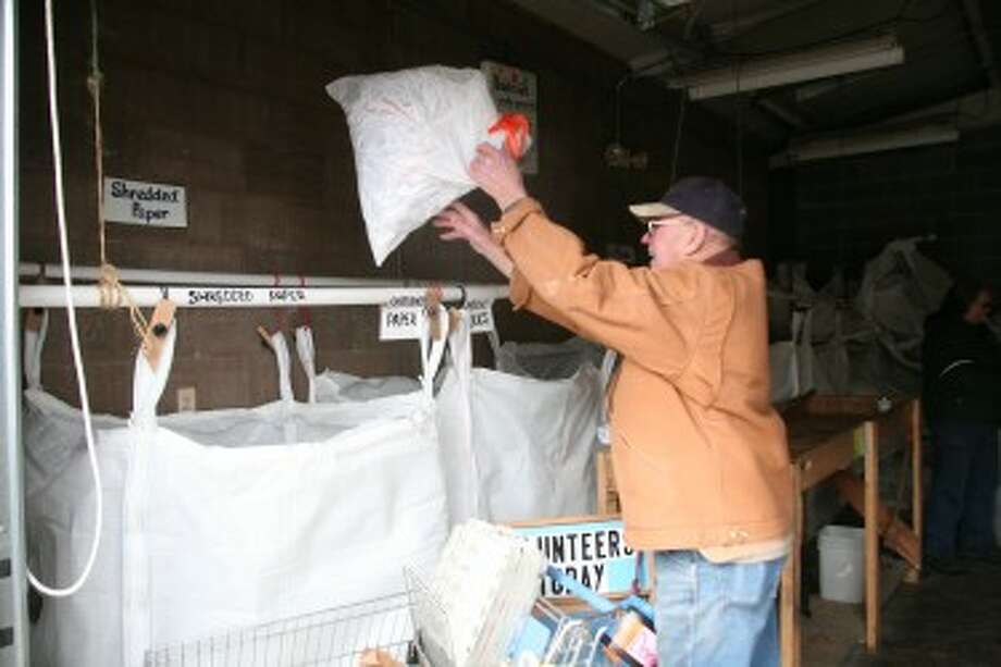 READY TO RECYCLE: Gil Heilman recycles a bag of shredded paper on Wednesday at Recycle of Osceola County. Heilman, Fay Wilson, Pat Kailing, Neil Tetzlaff, Ed Lazar and Art Proefrock were recognized for volunteering at the organization since it began 25 years ago.