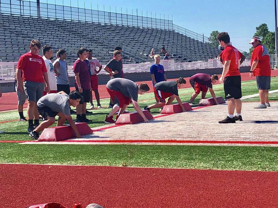 Defensive line coach Troy Fox runs a drill at Crosby Cougar Football Camp on July 25 at Cougar Stadium Photo: Elliott Lapin / Staff Photo