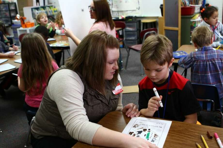 Ferris State University student Kristine Moulter (left) works with Riverview kindergartner Ethan Amyx on a worksheet as a portion of her final exam. (Pioneer photo/Meghan Gunther-Haas)