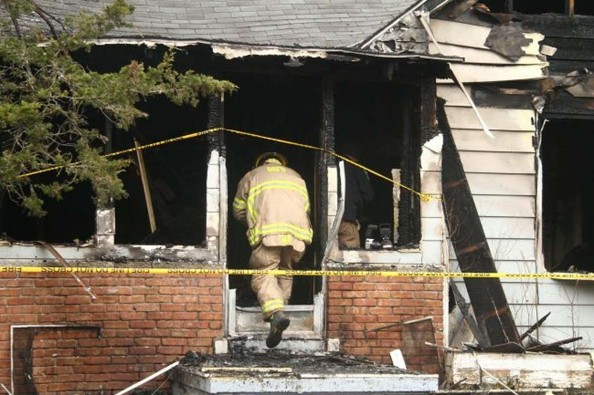 Investigators enter the home Monday on 132 South Bronson Avenue to determine the fire's cause. Georgia Bauman, 80, was pulled from the structure, but succumbed to her injuries. (Pioneer photos/Emily Grove)