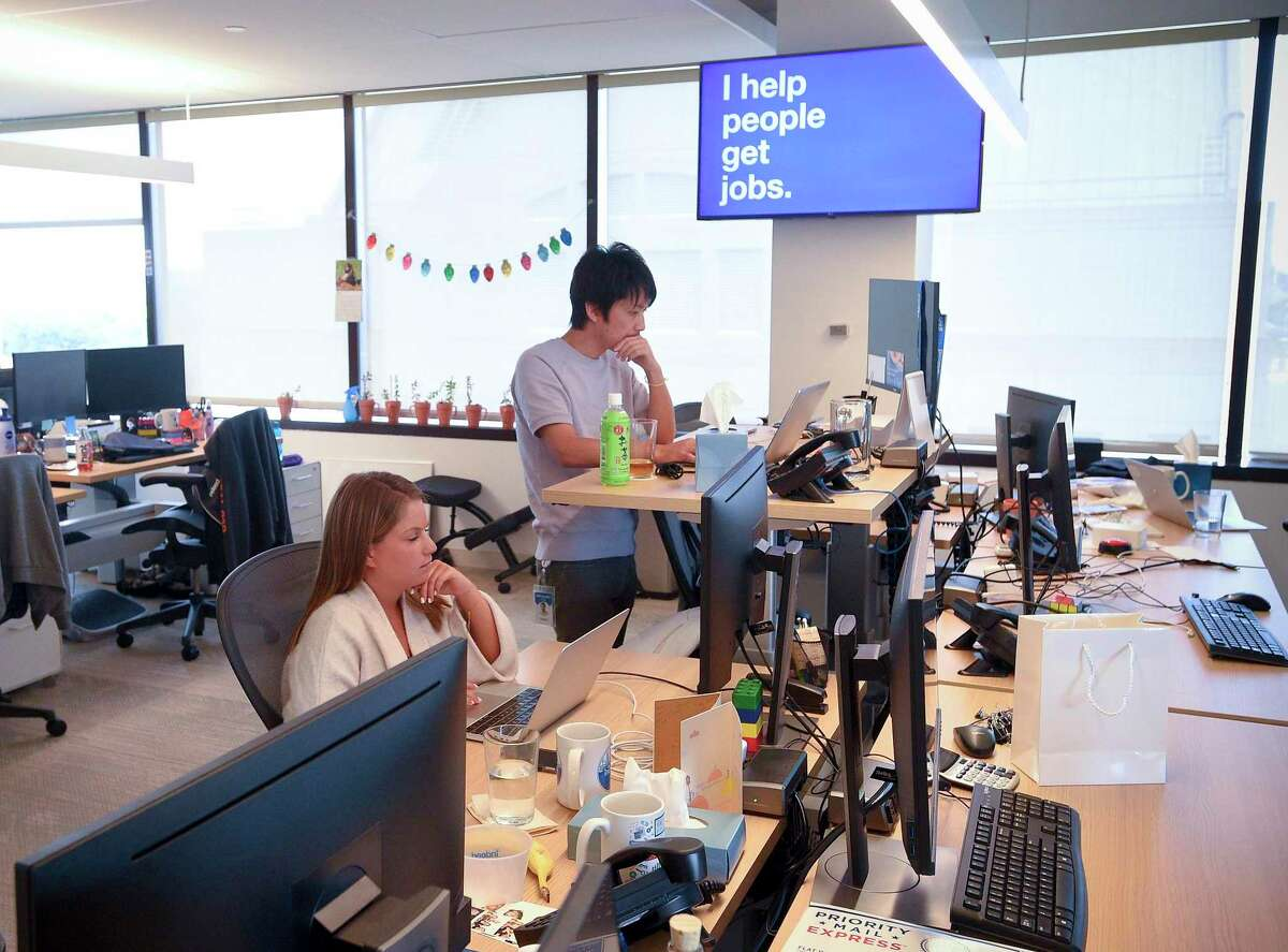 Employees of Indeed work at work stations at its Stamford offices on July 24, 2019. In response to the spread of the coronavirus, the company has told employees to work from home