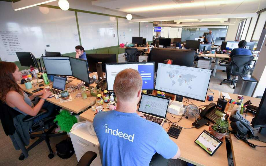"""Employees of Indeed.com work at work stations at its Stamford based offices on July 24, 2019. In response to the spread of the coronavirus, the company has told employees to work from home """"until further notice."""" Photo: Matthew Brown / Hearst Connecticut Media / Stamford Advocate"""