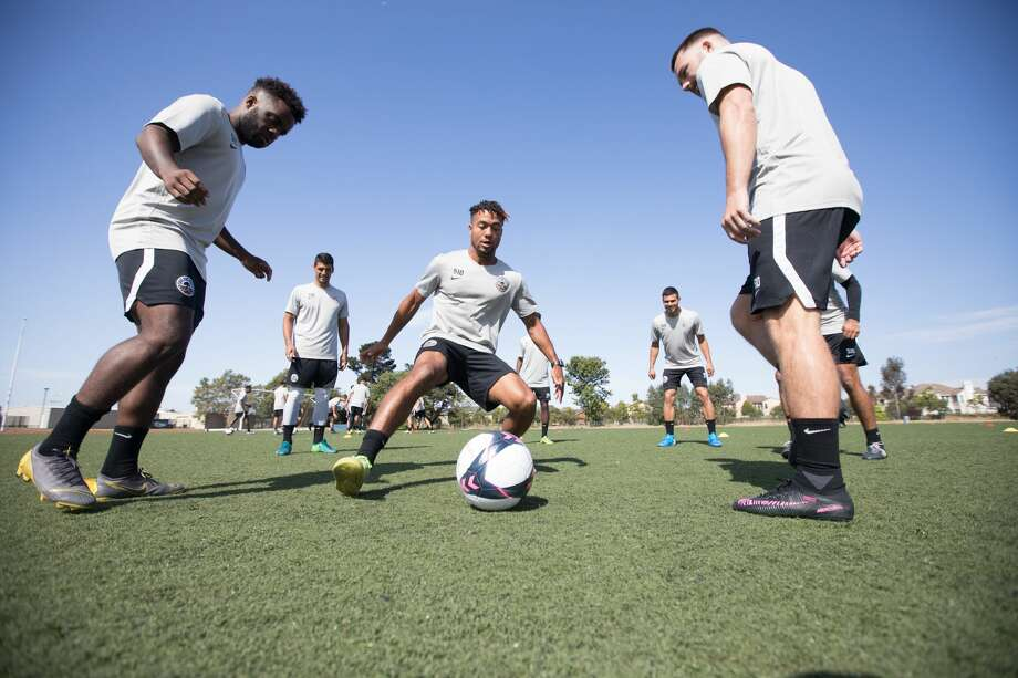 Oakland Roots' Devante Dubose (center) tries to intercept a ball during the club's first ever practice at the College of Alameda on July 25, 2019. Photo: Douglas Zimmerman/SFGate