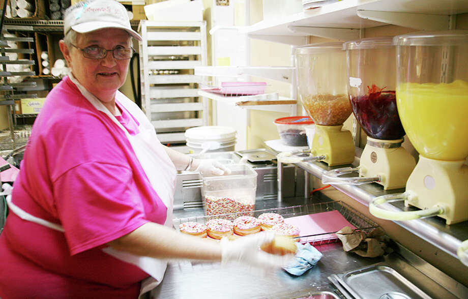 "FRESH DOUGHNUTS: Deb Eckert frosts and adds sprinkles to doughnuts at Bernie's Place on Friday; this part of the process is known as ""finishing"" the doughnuts. Eckert has worked at Bernie's for more than 25 years. (Pioneer photo/Lauren Fitch)"