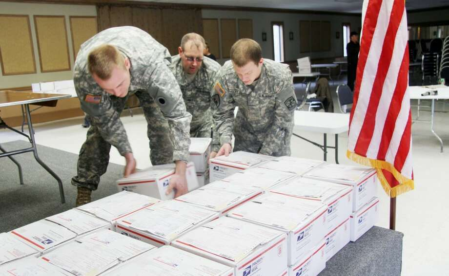 PACKED WITH CARE: Ferris State University ROTC students helped fill out custom forms for care packages sent to soldiers by Kelly's Deer Processing. More than 80 care packages were sent out containing 500 pounds of jerky and personal items. (Pioneer photos/Lauren Fitch)