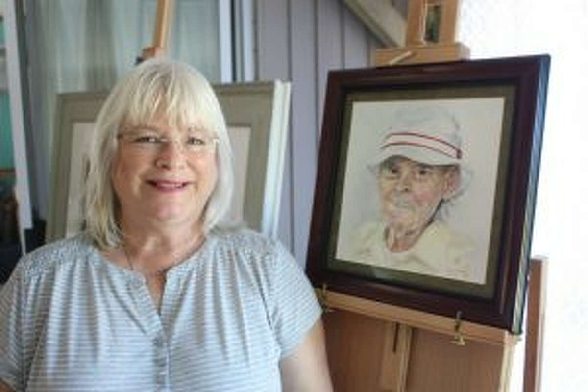Christine Kulikamp, of Big Prairie Township, poses beside her watercolor painting,