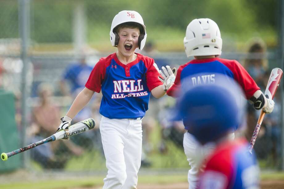Chester Sabin of Northeast Little League high-fives a teammate after scoring a run during the winner's bracket final of the minor Little League district tournament against Shepherd on Thursday, July 25, 2019 at the Fraternal Northwest Little League fields in Midland. (Katy Kildee/kkildee@mdn.net) Photo: (Katy Kildee/kkildee@mdn.net)