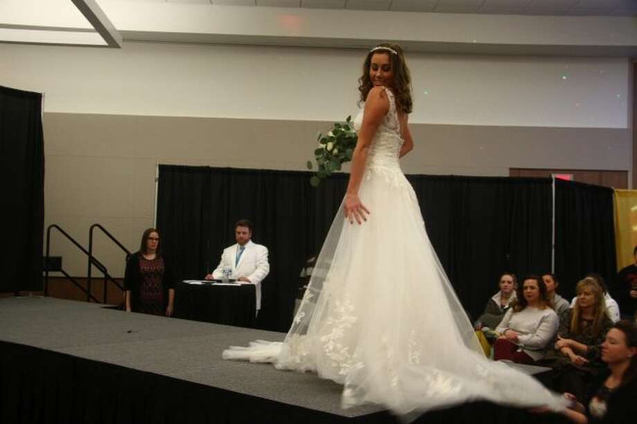 A model wears one of the wedding gowns from America's Bride during the fashion show Sunday at the annual Y-102 Bridal Show. Hundreds attended the event, which featured various local vendors who specialize in wedding-related services. (Pioneer photos/Emily Grove)
