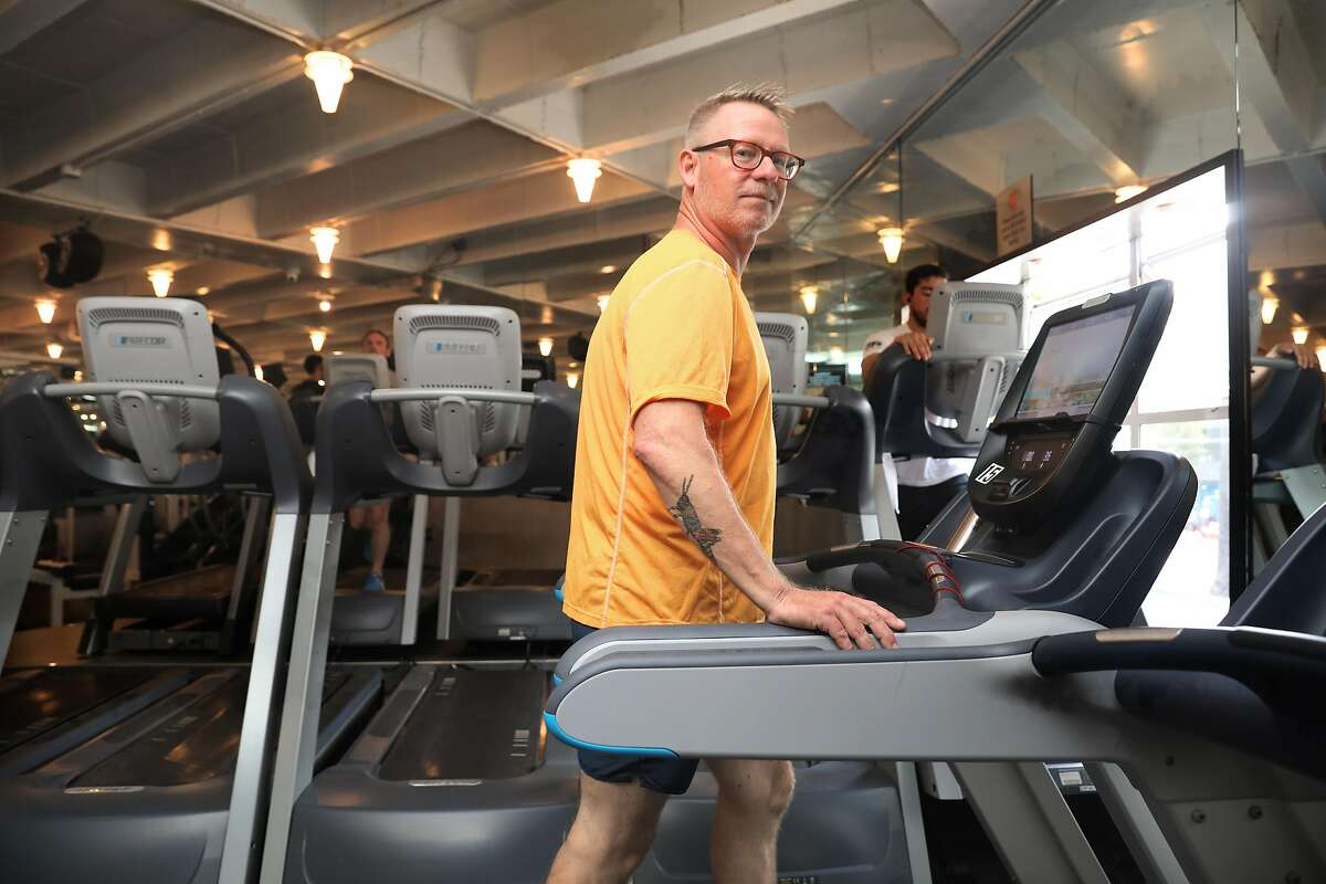 Kindergarten teacher Tim Simpson starts on the tread mill in the gym before his weight workout at Fitness SF Castro on Thursday, July 25, 2019 in San Francisco, Calif. The teacher had to pay for his own sub when he needed open heart surgery to fix a valve defect.