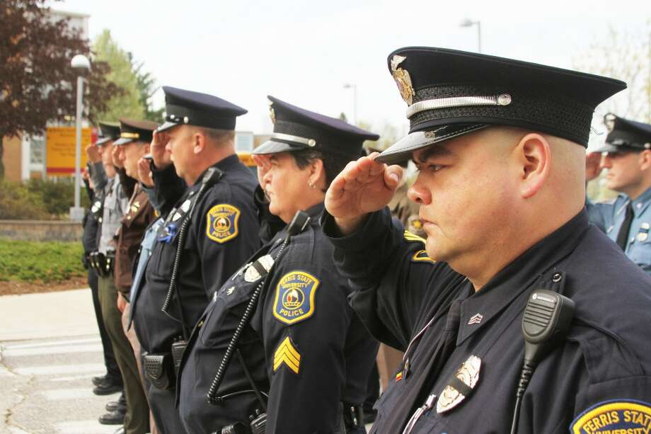 IN MEMORY: Officers from Ferris State University Department of Public Safety, Big Rapids Department of Public Safety and the Mecosta County Sheriff's Office salute as the flag is lowered to half-staff during Tuesday's Police Memorial Ceremony. (Pioneer photos/Whitney Gronski-Buffa and Josh Roesner)