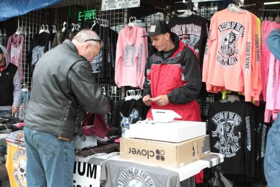 Gregory Davis (right) assists a customer at his booth during the Blessing of the Bikes. Davis works with Americas Bikers Inc., a T-shirt store based in Daytona Beach, Florida, which served as one of the main vendors of merchandise for the weekend-long event.