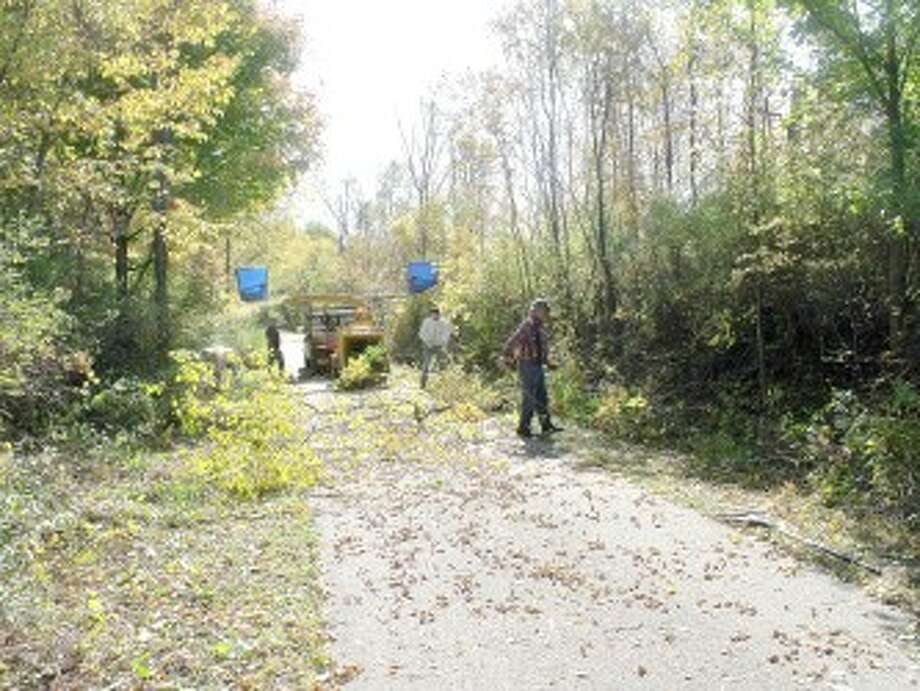 TRIMMING TREES: Members of the Pere Marquette Snowmobile Club trim new and old growth along the Pere Marquette Trail in anticipation of the upcoming snowmobile season. (Pioneer photo/Jim Crees)
