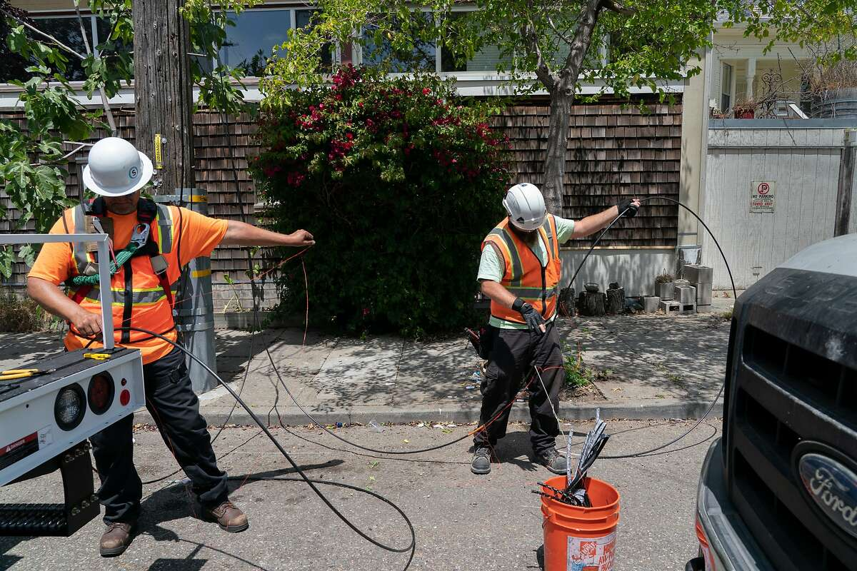 Sonic employees Francis Barton and Darrin Dailey installs new fiber optic cables at a box on Fairview St. and California St. that can provide 500 homes with symmetrical Gigabit speeds on Thursday, July 25, 2019, in Berkeley, Calif.