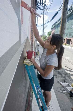 Mildred Paulino of Danbury, a former student of Escape To The Arts, volunteers to help Joe DiGuiseppi, a local artist, create a mural on the side of the Omaha Beef building on Crosby Street. Saturday, July 31, 2010 Photo: Scott Mullin / The News-Times Freelance
