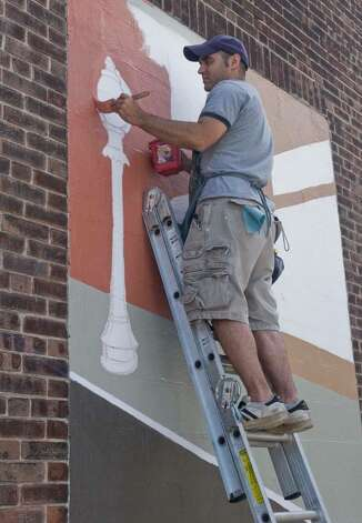 Joe DiGuiseppi, a local artist, creating a mural on the side of the Omaha Beef building on Crosby Street, paints one of the blocked in windows. Saturday, July 31, 2010 Photo: Scott Mullin / The News-Times Freelance