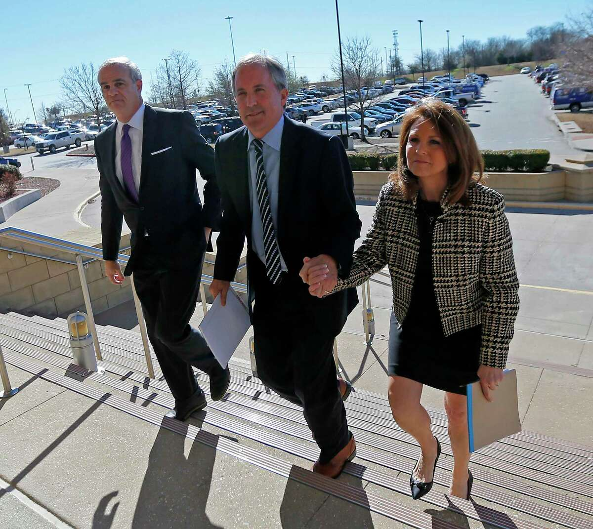 Texas Attorney General Ken Paxton (center) arrives the Collin County Courthouse with his wife Angela (right) and attorney Phillip Hilder for his pretrial hearing in McKinney, Texas, Thursday, Feb. 16, 2017. (Jae S. Lee/The Dallas Morning News)