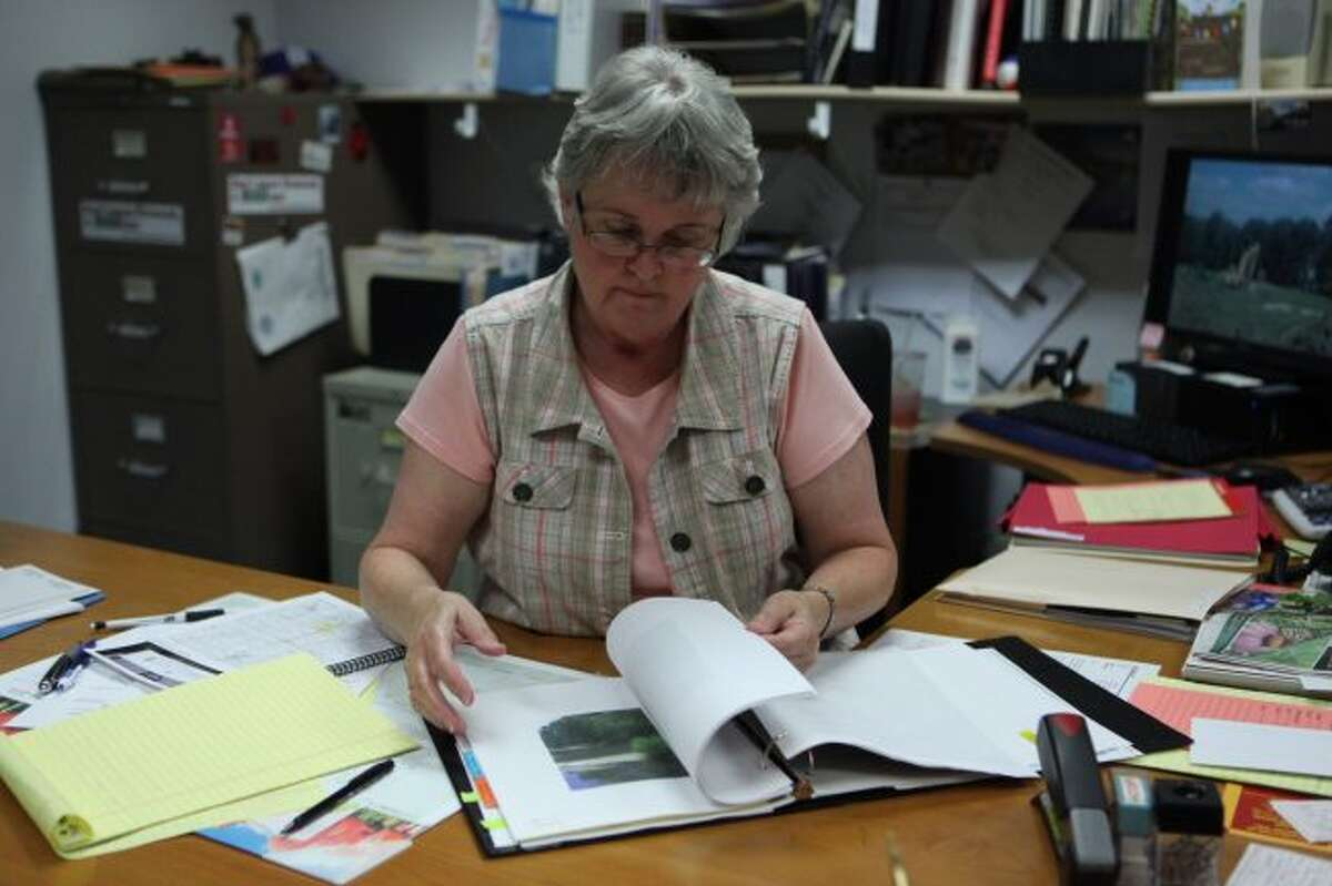 Mecosta County Drain Commissioner Jackie Fitzgerald looks through her files on the proposed Ives Drain. Fitzgerald has decided to retire and will be spending her time helping with her mother and her family's assisted living facility in Tustin. (Pioneer file photo)