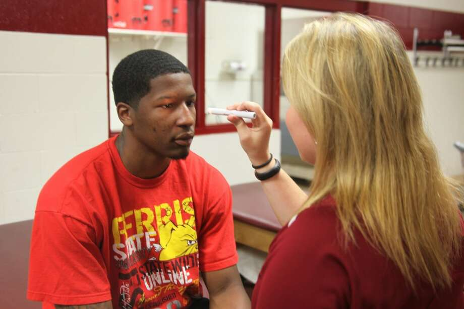 THIS IS A TEST: Ferris State assistant athletic trainer Kara Bremer demonstrates a test to Ferris State basketball player Daniel Sutherlin that would be administered to an athlete to determine whether they are still experiencing symptoms of a concussion. (Pioneer photo/Martin Slagter)