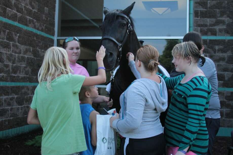 AN OLD FAVORITE: Children gather around to pet equine officer Boomer at Tuesday's National Night Out Event. Boomer is one of the favorite returning attractions to the annual event, said Linda Miller, Program Specialist for the Big Rapids Housing Commission. (Pioneer photos/Emily Grove-Davis)