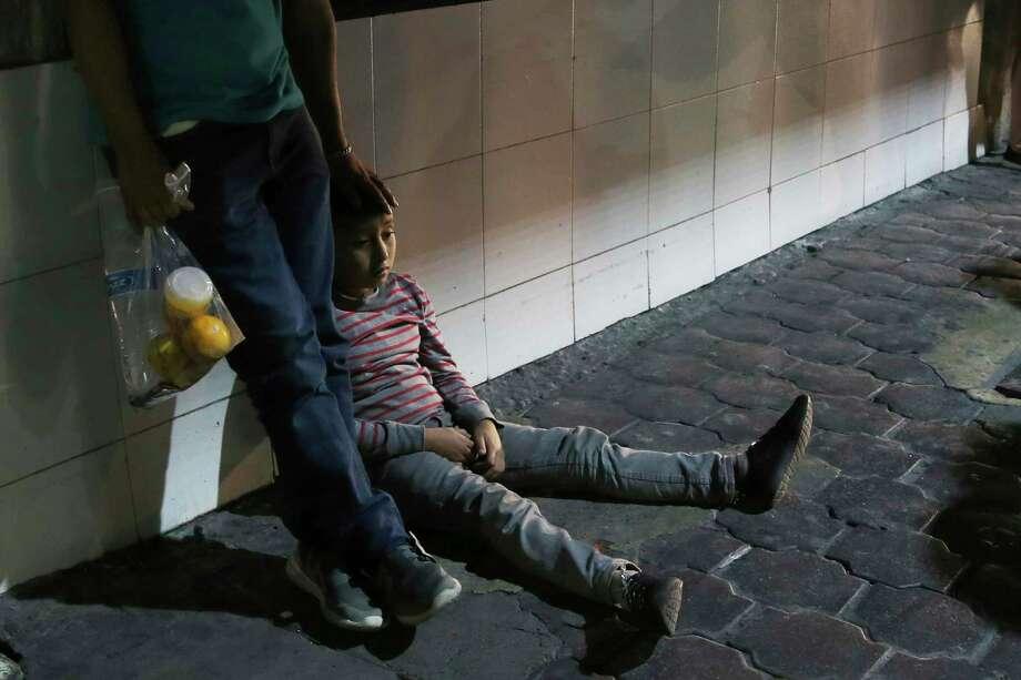 En esta imagen, tomada el 18 de julio de 2019, un niño migrante y su padre esperan junto luego de que las autoridades migratorias mexicanas los trasladaron en autobús desde Nuevo Laredo, en la frontera con Estados Unidos, a Monterrey, México. Photo: Marco Ugarte /Associated Press / Copyright 2019 The Associated Press. All rights reserved.