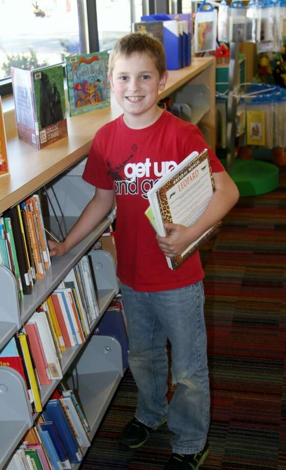 KIDS SPACE: Colby Bell, 11, looks for books about animals in the children's section of the Morton Township Library. (Pioneer photo/Lauren Fitch)