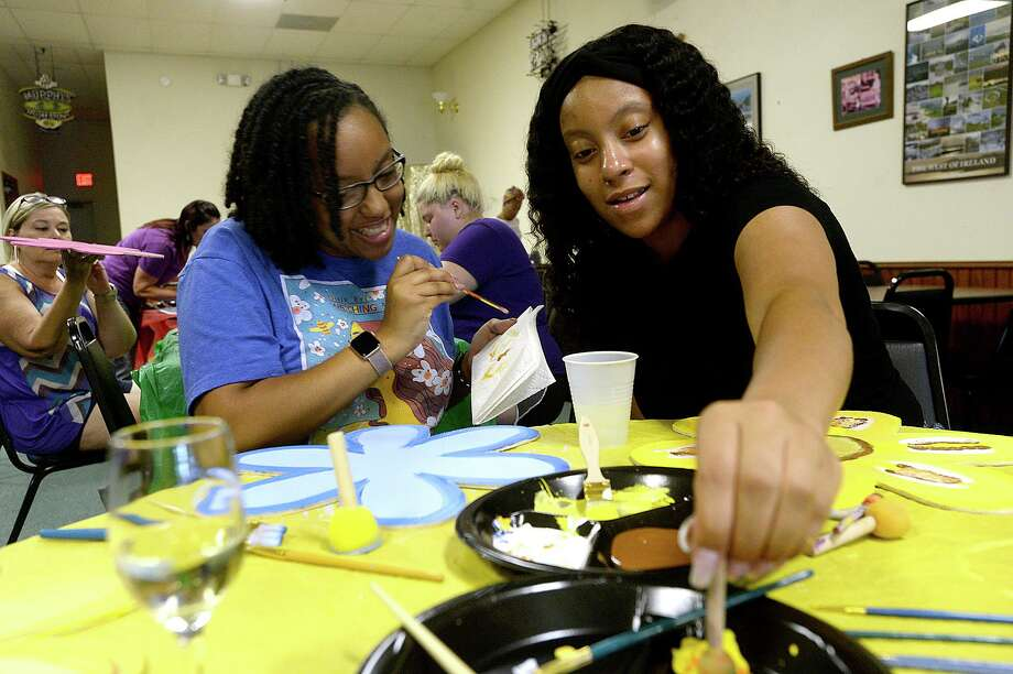 Jannah Mitchell (left) and Jaleah Mitchell talk as they work on painting their flowers during Painting at the Pub night at ther Clifton Steamboat Museum. Participants could enjoy wine and snacks while painting, with Thursday's project having a floral theme. The women, including Erica Mitchell (out of frame), took in the event while visiting with family from their home in Louisiana. Photo taken Thursday, July 25, 2019 Kim Brent/The Enterprise Photo: Kim Brent / Kim Brent / BEN