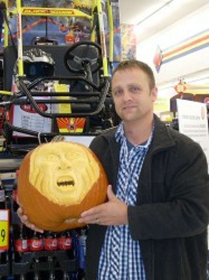 """BEST PUMPKIN: Ryan Butler with his """"Hands on Face Screaming Pumpkin"""" won first place in Leppink's Grocery's pumpkin decorating contest. He won the go-cart pictured at rear. (Courtesy photo)"""