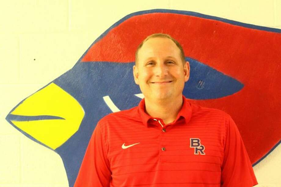 Josh Bull stands in front of the cardinals logo, ready to take on the role of principal at Big Rapids Middle School. He will be starting his new position in the fall. (Pioneer photo/ Catherine Sweeney)