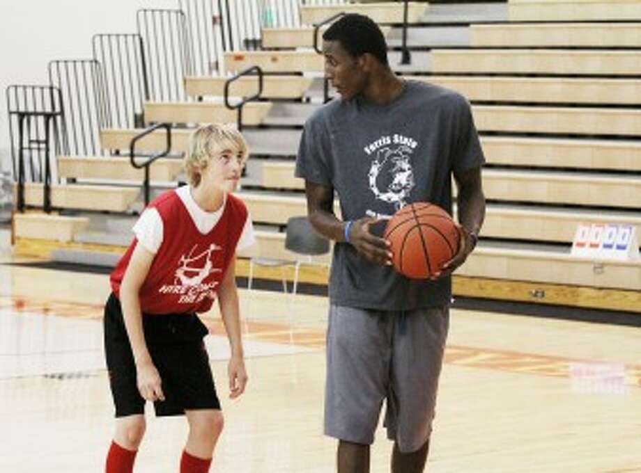 ATTENTION: Ferris State men's basketball player Raymoan McAfee (right) teaches hoops camper Ryan Kesting during a rebounding drill at the Boys Basketball Individual Skills Camp on Monday. (Pioneer photo/Martin Slagter)