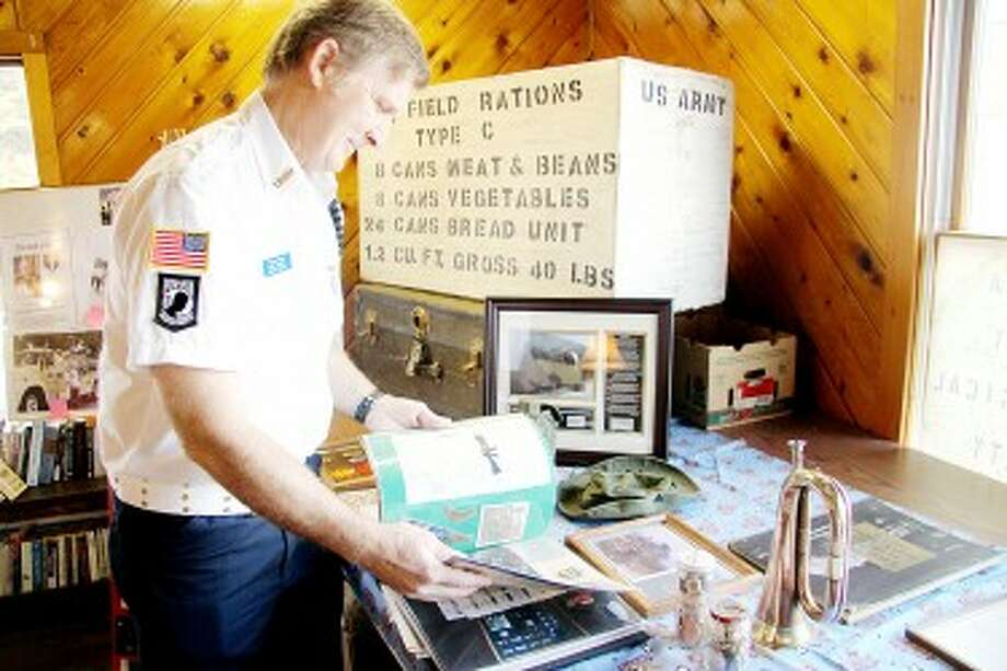 TRIBUTE: Duane Nelson, who served in the U.S. Marines Corps from 1973 to 1975, flips through a scrapbook last year. Local military veterans will participate in the fourth annual Veterans Tribute on Saturday at the Mecosta County Genealogical Society. (Pioneer file photos)