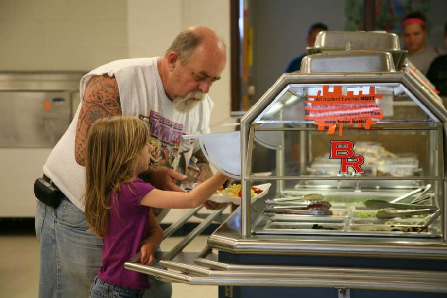 SUMMER MEALS: Big Rapids resident Tim Porter helps his daughter Hannah Porter, 6, make a selection from the salad bar at Big Rapids Middle School on Tuesday. BRMS is just one of the four sites in Mecosta County participating in the federally funded summer meals program. (Pioneer photo/Alex Wittman)