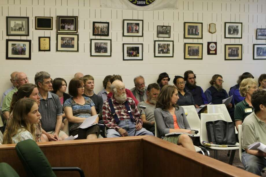 Audience members look on as Mecosta County Administrator Paul Bullock speaks during the Thursday evening county commission meeting.