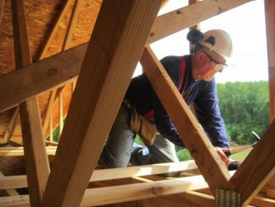 BUILD: A volunteer kneels on beams as he focuses on the task at hand. (Courtesy photo)