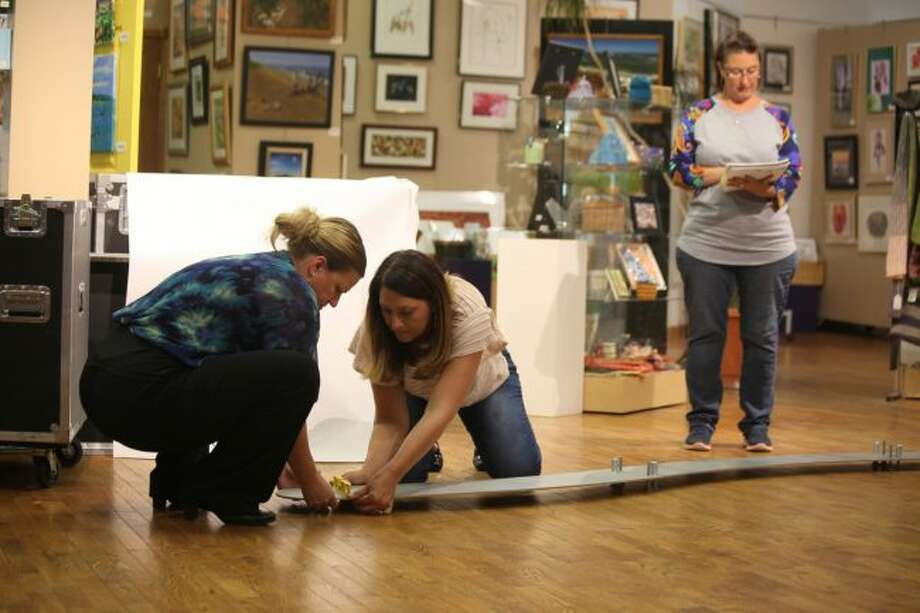 "(From left) Jennifer Heinzman, Arlene Anderson-Vincent and Lisa Besemer helped set up the ""Water/Ways"" exhibit at Artworks."