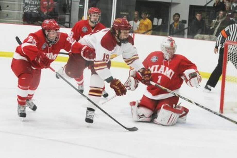 GET IT: Ferris State's Justin DeMartino (19) pursues the puck along with Miami's Blake Coleman (left) and goaltender Jay Williams. Ferris State fell to the Red Hawks, 4-2. (Pioneer photo/Martin Slagter)