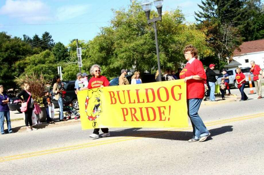 People flocked to Michigan Avenue on Saturday to watch the Ferris State University homecoming parade.Ferris staff and faculty lead the band through town. Band members sat on hay bales stacked on a truck bed while playing. (Pioneer photos/Meghan Haas)
