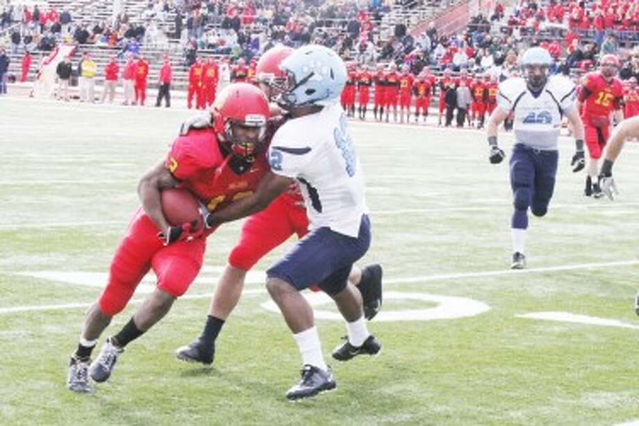 TACKLED: Ferris State slot back Dwayne Williams (left) is tackled by a Northwood player during Saturday's football game. (Pioneer photo/Martin Slagter)