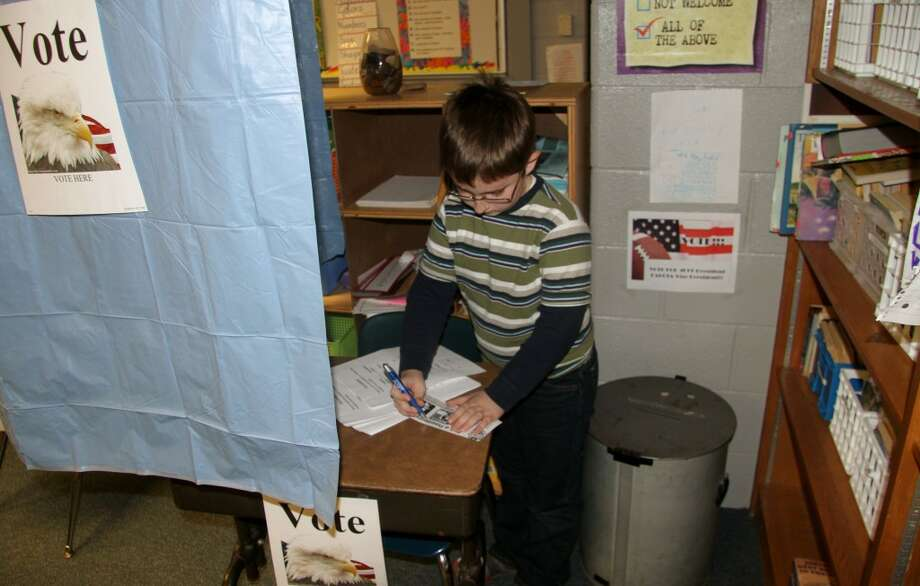 CAMPAIGN SEASON: Galen Switzer, a fourth grader at Brookside Elementary School, votes for one of his classmates as president. The students gave speeches on Tuesday.