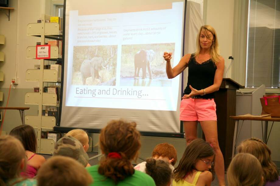 SAFARI IN THE LIBRARY: Michelle Lee shows children about how much a gallon is by comparing it to a gallon of water, while explaining how much elephants eat on Tuesday, June 25 at the Big Rapids Public Library. (Pioneer Photo/Eric Dresden)