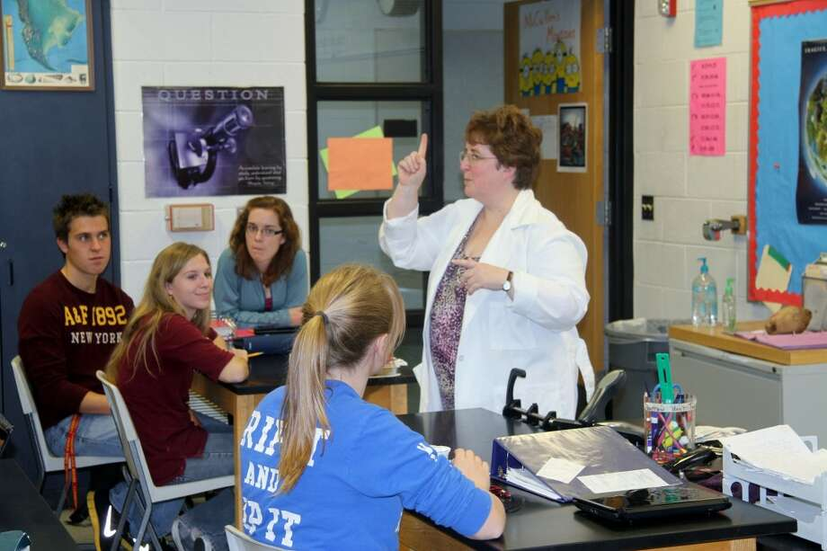 "INNOVATIVE TEACHING: Sue McCullen teaches her AP biology class at Big Rapids High School. This year, McCullen adopted a ""flipped"" approach, where students watch videos of her lecture at home and spend class time going over homework and completing labs. (Pioneer photos/Lauren Fitch)"