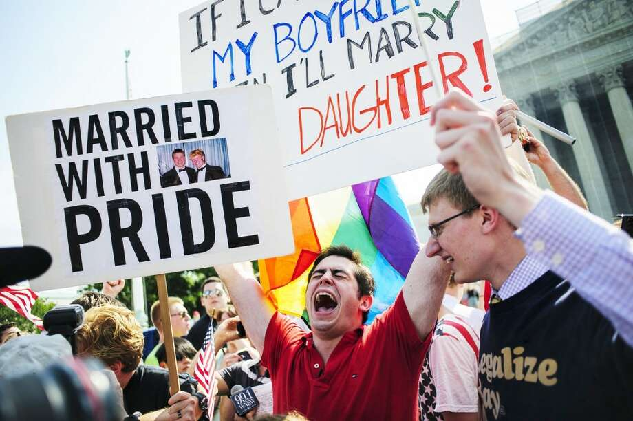 David Baker, 24, center, of Phoenix, Arizona, celebrates outside the Supreme Court after hearing that the Court struck down the Defense of Marriage Act, Wednesday, June 26, 2013, in Washington, D.C. (Pete Marovich/MCT)