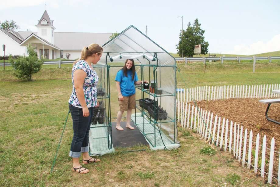 SUMMER CAMP: Stephanie Dood steps inside the greenhouse donated for Big Jackson's free summer camp while Jessica Leenhouts looks on. (Pioneer photos/Alex Wittman)