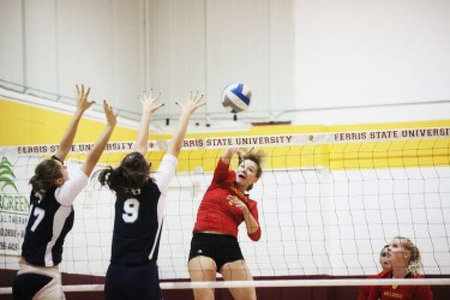 OUT OF REACH: Ferris State's Megan Vander Meer hits the ball past a pair of Northwood defenders during Saturday's 3-0 victory over the Timberwolves. (Pioneer photo/Bob Allan)