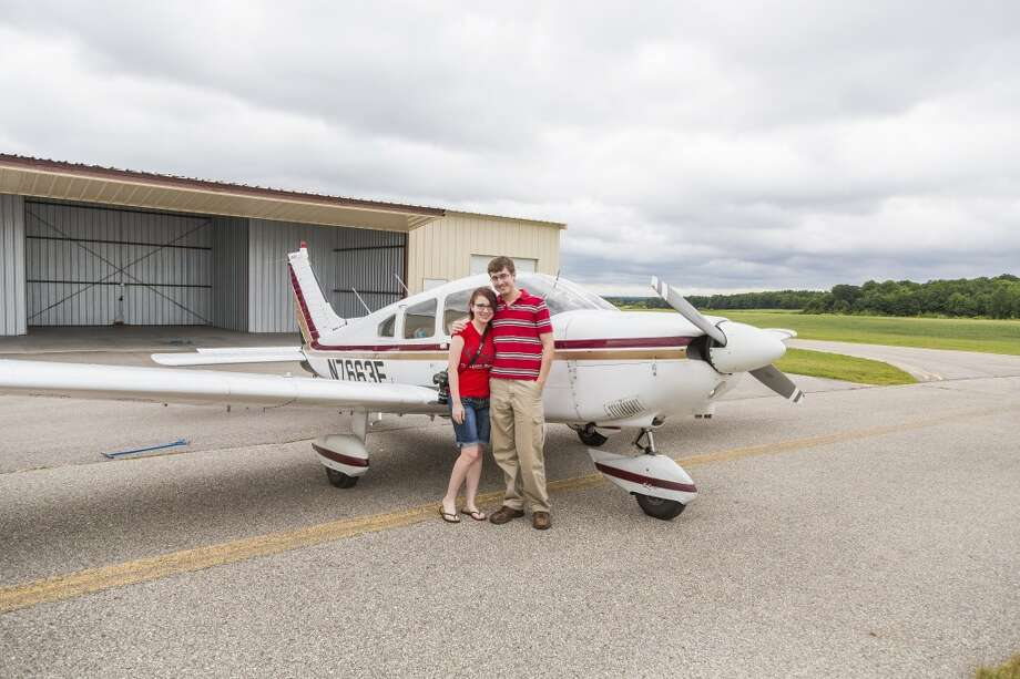 HIGH FLYING TIME: Justin McKee (right) and his girlfriend Sarah Burns stand in front of a small airplane at Roben-Hood airport in Big Rapids. (Pioneer photos/Justin McKee)