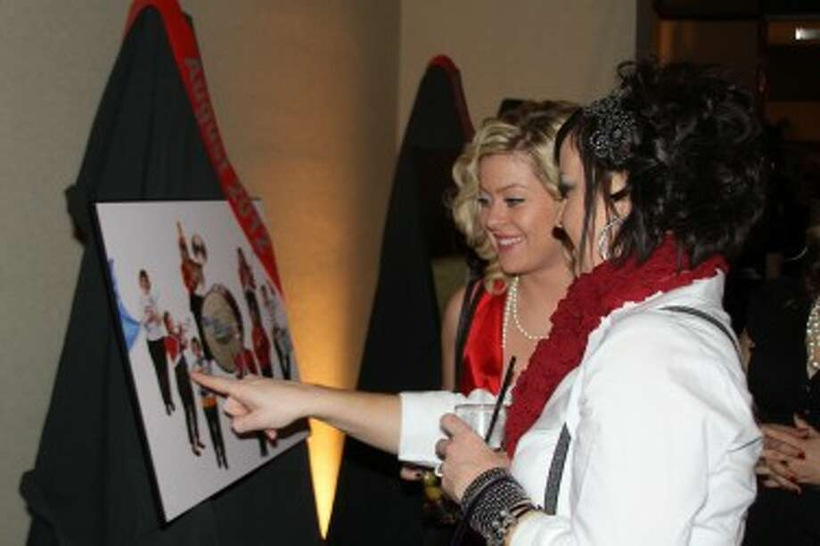 HOLIDAY GALA: Attendees at the 2011 look at images from the Dames Through the Decade calendar project. The 2012 gala will be held on Dec. 7 at the Holiday Inn Hotel. (Pioneer file photo)