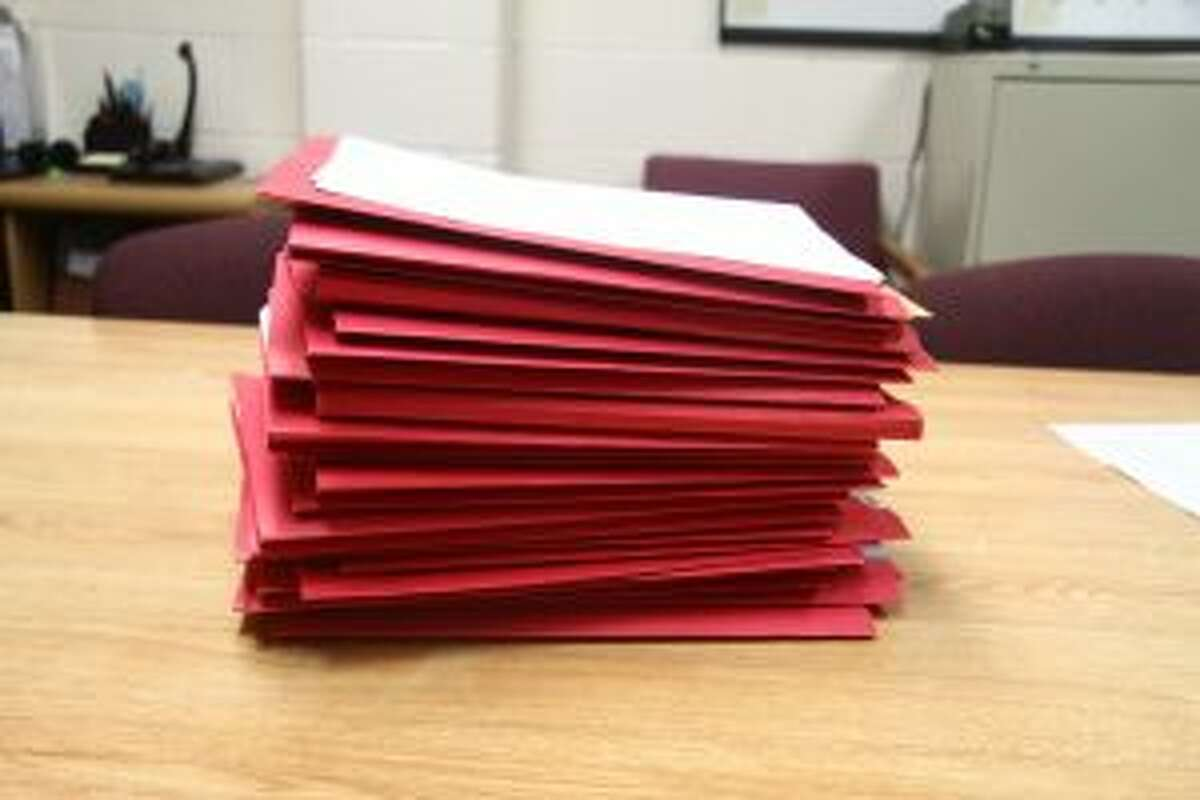 A stack of case files sits on a table in the Mecosta County Prosecutor's Office.