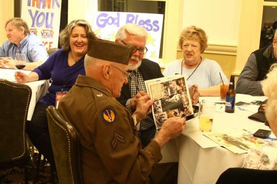 Richard Pilon flips through a photo book at last year's Tour of Duty fundraiser, showing the pictures to Charles Schunck and others at his table. This year's event will be Sunday, Oct. 15, at the University Center on Ferris State University's campus. (Pioneer file photo)