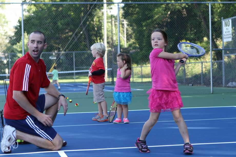 LEARNING THE GAME: Ferris State University Associate Athletic Director Jon Coles and Taylor Chatel watch a tennis ball Chatel hit go across the tennis court on Wednesday during a tennis camp going on at Hemlock Park. (Pioneer photos/Eric Dresden)