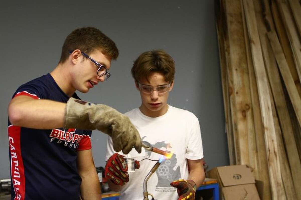 Joey Dennis (left) teaches Big Rapids eighth-grader Alec Bollman about soldering during Manufacturing Day on Friday, at the Mecosta-Osceola Career Center. (Pioneer photo/Meghan Haas)